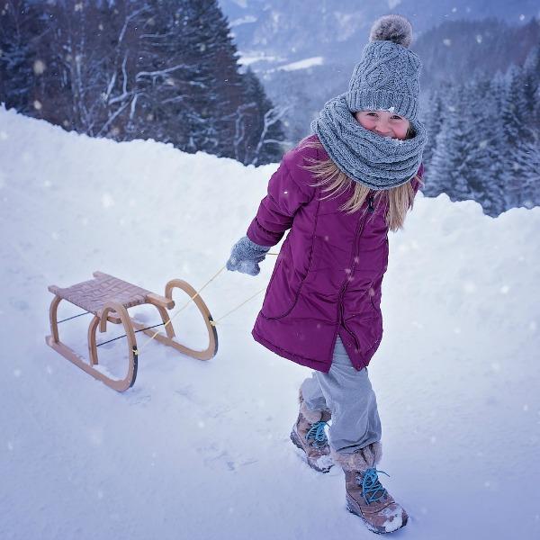 Meisje met slee in de sneeuw, illustratie warmtezin